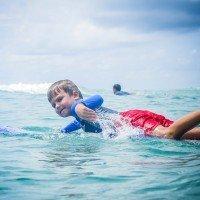 Фото мальчик серфер гребет на лайнап в русском серф кемпе Endless Summer