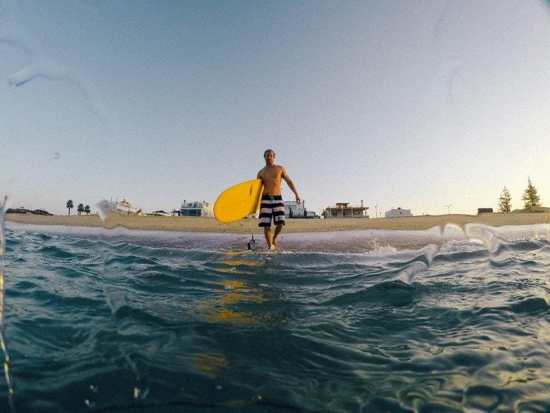 Изображение человека с доской для сёрфинга